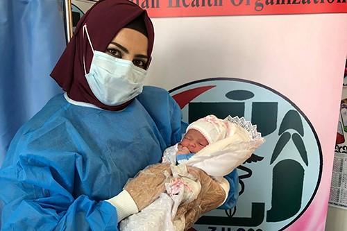 هورين يوسف تحمل المولود الذي انقذت حياته في سيارة إسعاف. © زيان