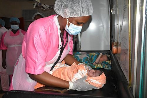 قابلة في المركز الطبي المجتمعي في ماتام تلف الأطفال حديثي الولادة في بطانيات دافئة. © صندوق الأمم المتحدة للسكان، غينيا