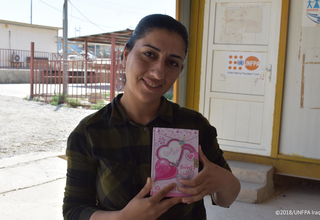 Sana' holding her notebook where she writes down her most cherished memories since she arrived to Iraq.  © UNFPA Iraq/Salwa Moussa