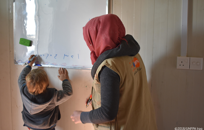 """Many women desire children, and face disappointment or even stigma if they cannot. A UNFPA-supported counselor watches over a refugee child in Iraq. © 2018/ UNFPA Iraq"