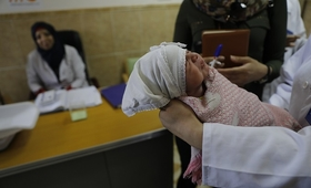 Hospital Midwife holds new born baby in West Mosul