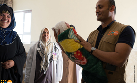 UNFPA Representative in Iraq, Ramanathan Balakrishnan, carrying a new born baby that was delivered during his field visit to Qayyarah delivery room.